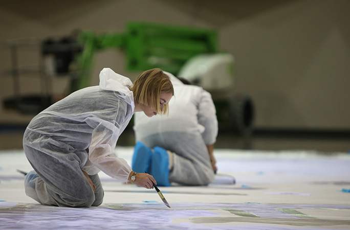 Young Minds employee painting the canvas.jpg