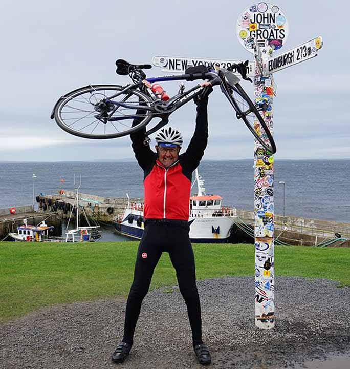 alex-at-john-o-groats-holding-bike-above-head.jpg